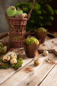 Ostereier und muffins mit pistazien in traditionellem rustikalem design. grüne pflanzen und federn
