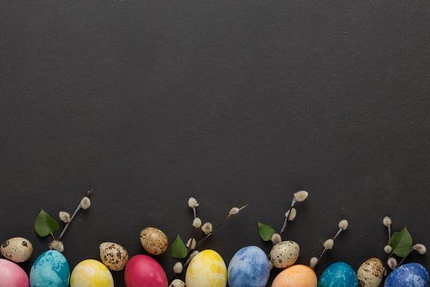 Ostereier und weidenkätzchenzweige auf einem dunklen hintergrund
