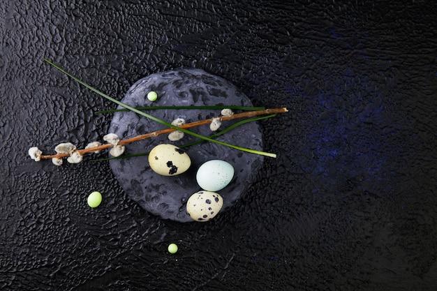 Ostereier und weidenkätzchenzweige stehen auf einem runden schieferstein