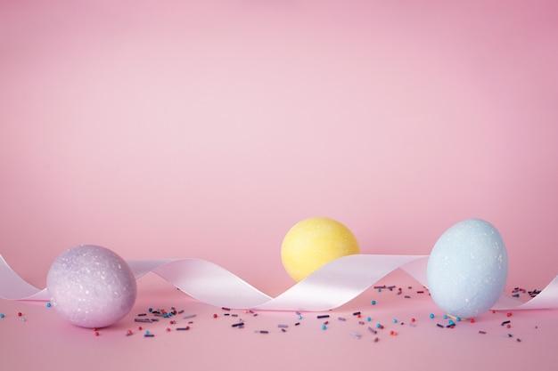 Ostereier und weißes band auf einem rosa hintergrund, platz für text. frohe ostern konzept.