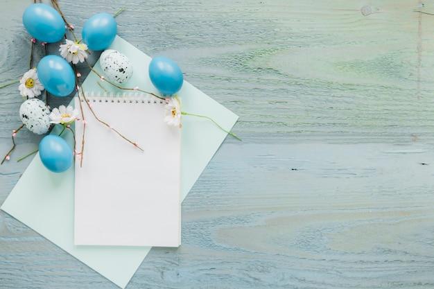 Ostereier und zweige in der nähe von notebook