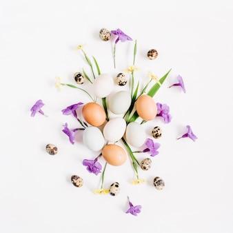 Ostereier, wachteleier, gelbe und lila blüten auf weißer oberfläche