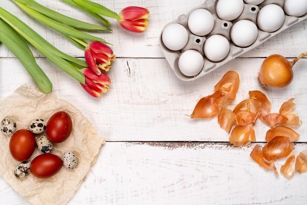 Ostereier werden mit natürlichem eierfarbstoff aus obst und gemüse bemalt, eier werden mit zwiebelschalen auf einem weißen holztisch und roten tulpen bemalt, kopierraum