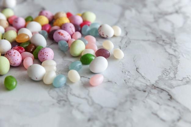 Ostereierschokoladeneier und geleebonbons auf trendigem grauem marmortisch