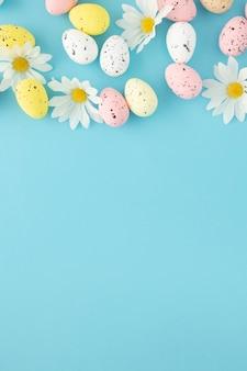 Ostereinladung mit eiern und gänseblümchen auf einem blauen hintergrund mit kopienraum