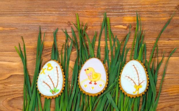 Ostereiplätzchen bedeckt mit zuckerguss auf einem hölzernen hintergrund mit grünem gras