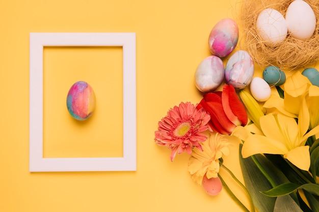 Ostereiweiß-grenzrahmen mit frischen blumen und eiern nisten auf gelbem hintergrund