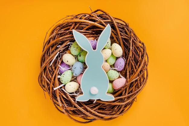 Osterfarbene eier und holzkaninchen liegen in einem holzkranz auf gelbem grund
