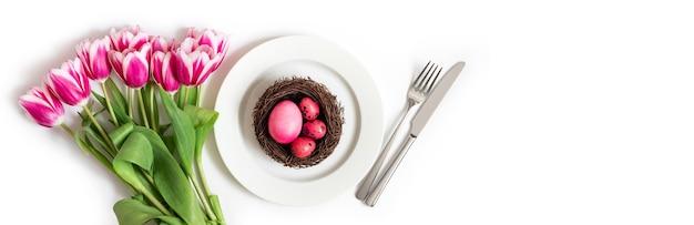 Osterfeiertagstabelleneinstellung mit rosa eiern in einem nest und tulpenblumen auf einem weißen hintergrund. banner. speicherplatz kopieren, draufsicht.