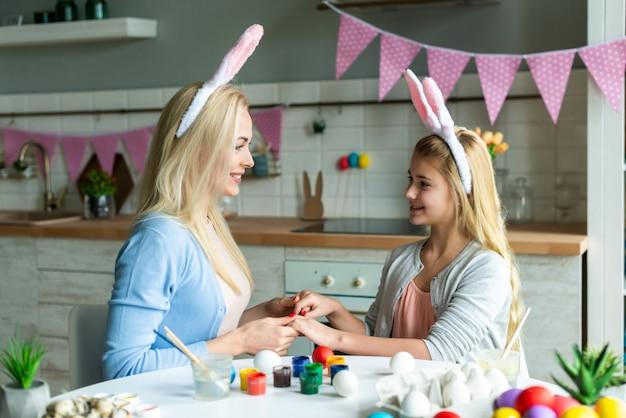 Osterferien, ostertag, glückliche familie, feiertagskonzept, mutter und töchter, die ostereier malen. glückliche familie, die sich auf ostern vorbereitet. mama und ihre mädchen spielen zusammen
