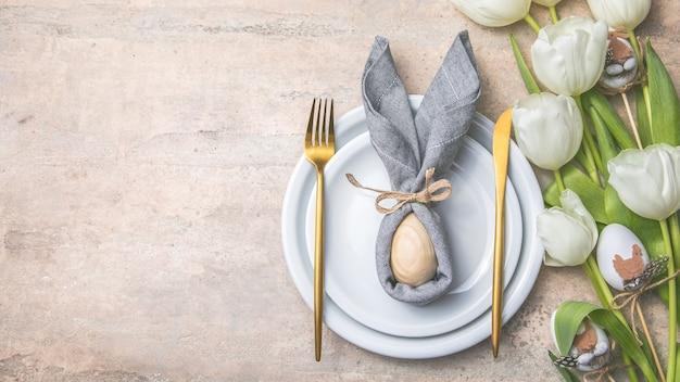 Osterferien-tabelleneinstellung mit hase vom ei auf weißem teller und tulpenblumen.