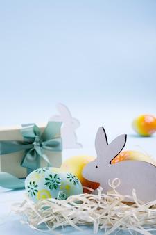 Osterferienhintergrund bunt bemalte hühnereier, weißer holzhase und geschenkbox mit band. osterferiendekorzusammensetzung
