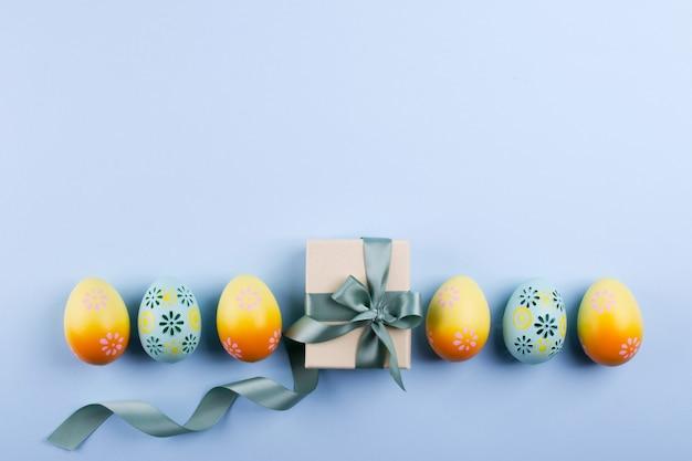 Osterferienhintergrund draufsicht von bunt bemalten hühnereiern, die in einer reihe und geschenkbox mit band plattiert werden