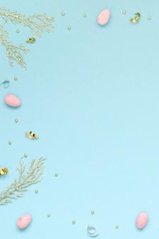 Osterferienhintergrund mit rosa ostereiern, goldenen zweigen und dekor auf einem blauen hintergrund. speicherplatzhintergrund kopieren. flach liegen.