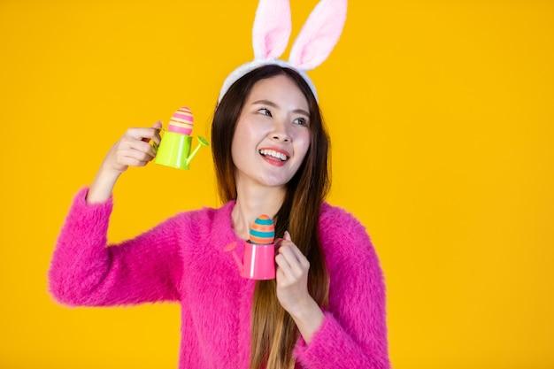 Osterferienkonzept, glückliches lächeln asiatische junge frau mit hasenohren, die mit kleinen gießkannen zu bunten ostereiern und den seitlichen augen in die kamera schaut, isoliert auf gelber leerer kopie