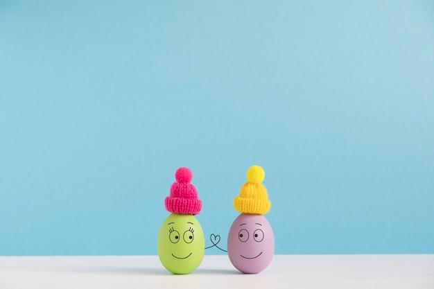Osterferienkonzept mit niedlichen eiern mit lustigen gesichtern. unterschiedliche emotionen und gefühle. schönes paar in hüten händchen haltend.