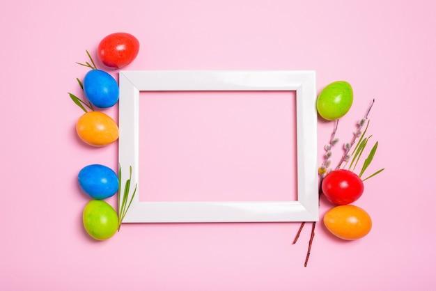 Osterferienweidenzweige und bunt gemalter eier-fotorahmen auf einer pastellrosa oberfläche.