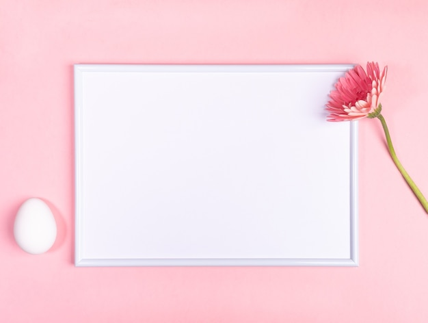 Osterfestes minimales konzept mit rahmen mit weißem kopienraum, einem weißen ei und gerberablume auf pastellrosa hintergrund.
