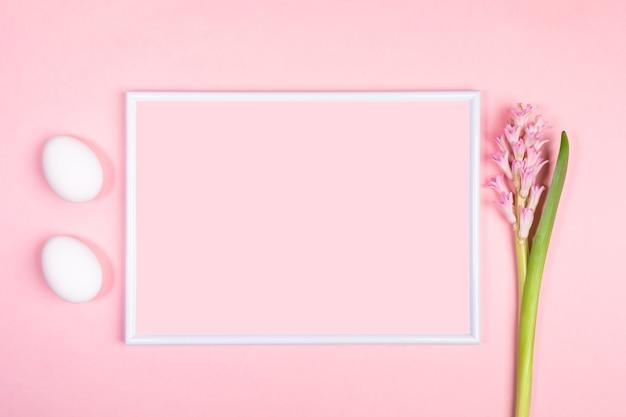 Osterfestes minimales konzept mit weißem rahmen, zwei weißen eiern und hyazinthenblume auf pastellrosa hintergrund.