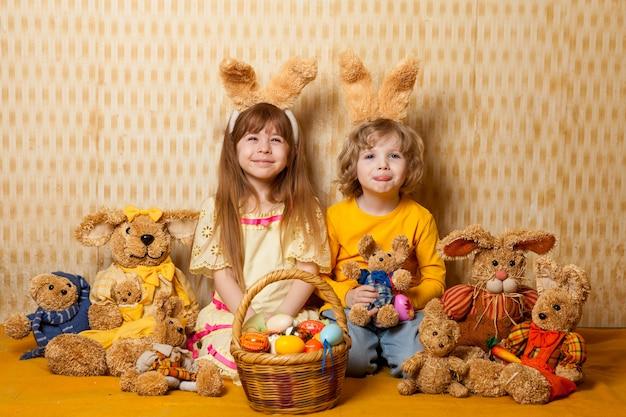 Osterfoto von emotionalen kindern mit einem korb von eiern mit hasenohren