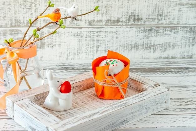 Osterfrühlingskomposition mit bemalten eiern, keramikhäschen und kleinen vögeln auf zweigen. festliche dekoration für die osterfeiertage mit leckerem osterkuchen oder kulitch.