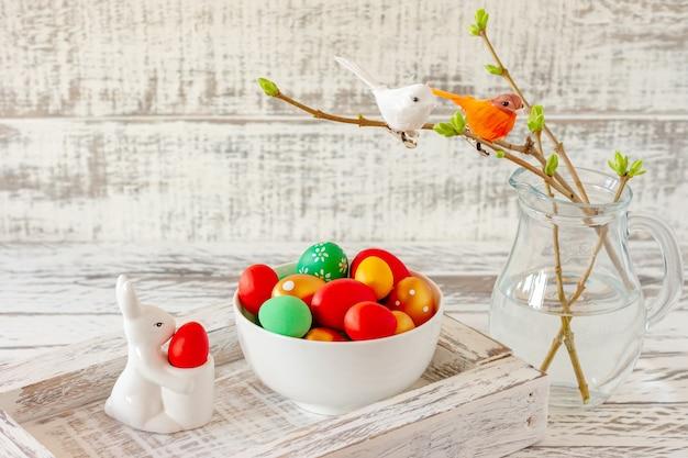 Osterfrühlingskomposition mit bemalten eiern, keramikhäschen und kleinen vögeln auf zweigen. festliche dekoration für die osterferien.