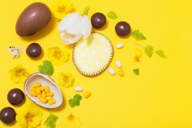 Ostergelber hintergrund mit schokoladeneiern, süßigkeiten und spri