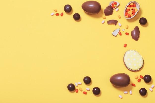 Ostergelber hintergrund mit schokoladeneiern und süßigkeiten
