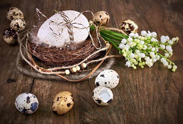 Ostergesteck mit eiern, nest und maiglöckchenblüten