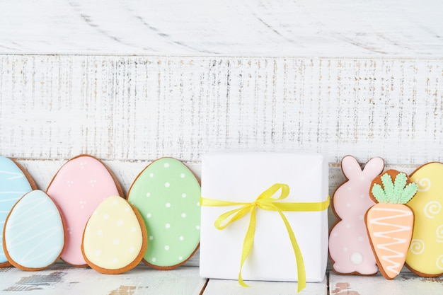 Ostergrußkarte mit bunten kaninchen, eiern, hühnern und karotten-lebkuchenplätzchen auf weißem altem holzhintergrund mit kopienraum. attrappe, lehrmodell, simulation. banner. ansicht von oben.