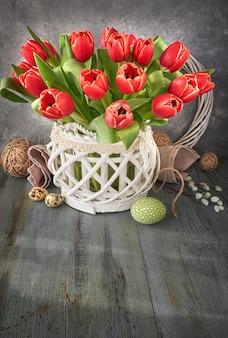 Ostergrußkartenentwurf mit bündel roter tulpen auf rustikaler wand mit osterdekorationen, textraum