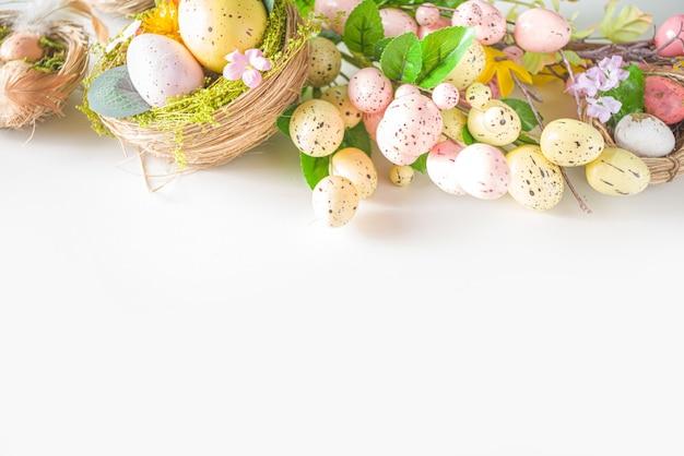 Ostergrußkartenhintergrund. frühlingsbaumdekorzweige mit bunten eiern, blumen und blättern auf weißem hintergrund kopieren platz für ihren text