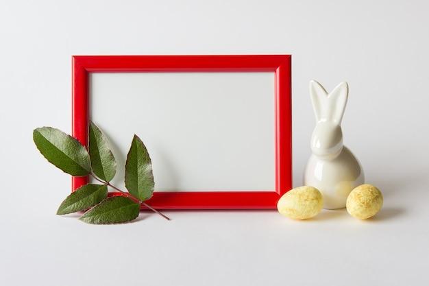 Ostergrußzusammensetzung mit rotem holzrahmen, porzellanhasen und eiern und grünem zweig.