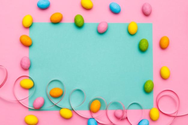 Osterhase. frohes osterferienhintergrundkonzept. flaches gelegtes buntes häschenei mit zubehör zur feier auf modernem rustikalem rosa pastellpapier am schreibtisch zu hause.