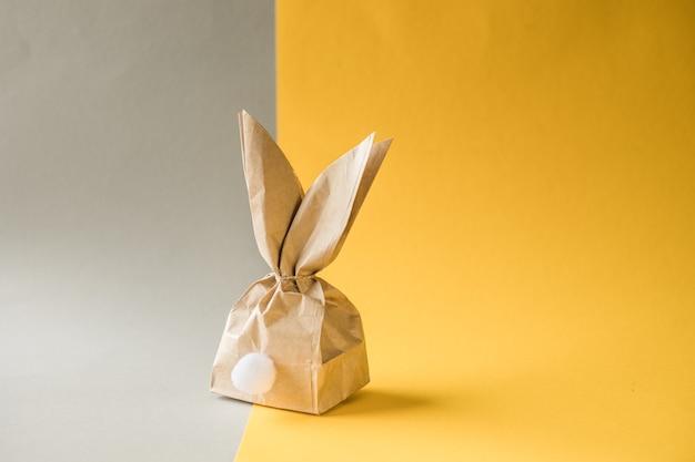 Osterhasenpapiergeschenk-eierverpackungs-diy-idee auf buntem hintergrund. minimales osterkonzept, flache lage, kopierraum
