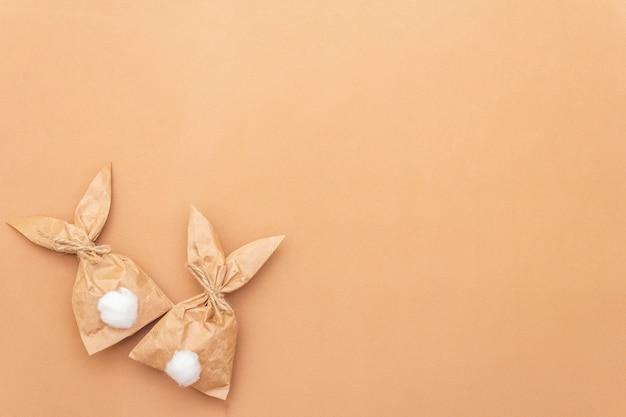 Osterhasenpapiergeschenk-eierverpackungs-diy-idee auf buntem hintergrund. minimales osterkonzept, flache lage, kopierraum.