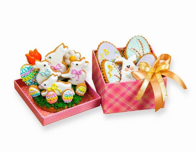 Osterhasenplätzchen und bunte eier in geschenkboxen. auf einem weißen hintergrund isoliert
