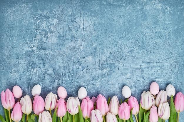 Osterhintergrund. dekorative ostereier und rosa tulpen. weihnachtskarte, kopierplatz.