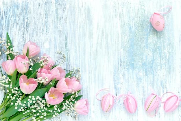Osterhintergrund. dekorative rosa ostereier und rosa tulpen auf blauem hintergrund. kopieren sie den speicherplatz oben
