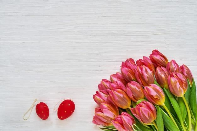 Osterhintergrund. deorative ostereier und rosa tulpen auf weißem hintergrund. speicherplatz kopieren, draufsicht.