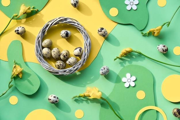 Osterhintergrund in grün und gelb. flache lage, draufsicht mit wachteleiern, rattankranz und frischen freesienblüten.
