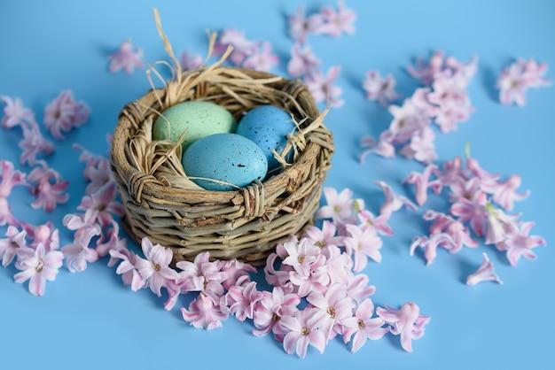 Osterhintergrund mit blauen ostereiern im nest der frühlingsblumen