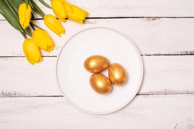 Osterhintergrund mit blauen und weißen eiern im nest und in den gelben tulpen. draufsicht mit kopierraum