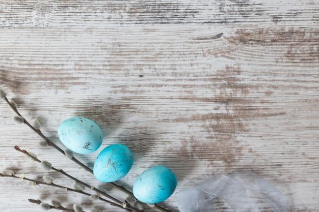 Osterhintergrund mit eiern auf einem weißen holztisch. von oben betrachten