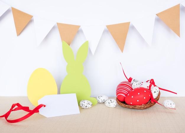 Osterhintergrund mit eiern, kaninchen und girlandenflaggen