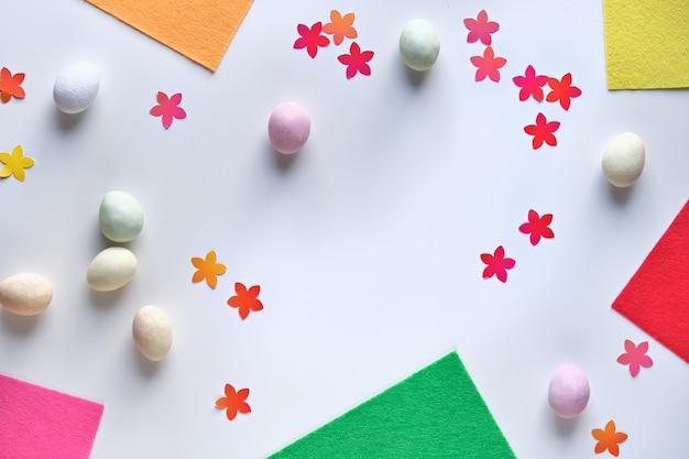 Osterhintergrund mit marzipan-ostereiern, papierblumenkonfetti und -stücken