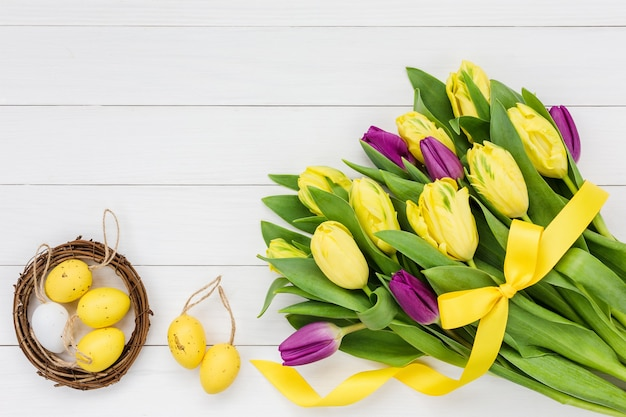 Osterhintergrund. strauß tulpen und dekorative ostereier auf weißem hölzernem hintergrund