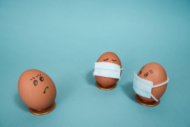 Osterhühnereier in medizinischen masken mit bösen gesichtsausdrücken neben einem hustenei