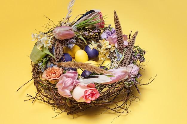 Osterkarte. gemalte ostereier im nest auf gelb