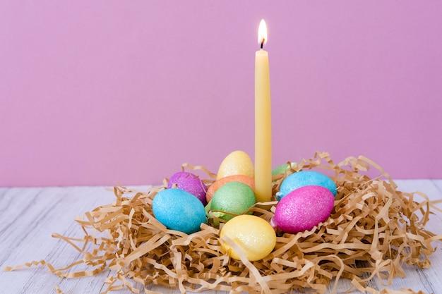 Osterkarte mit nest, farbigen eiern und brennender wachskerze auf lila pastellhintergrund